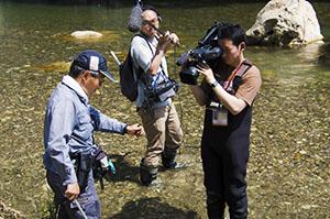 カジカガエルを手にしながら説明する当社社員(写真左)